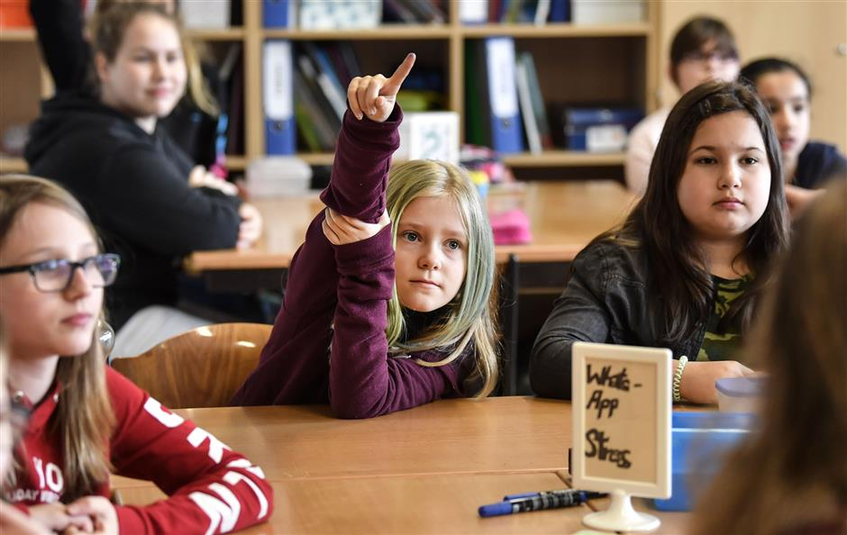 Pupil Vanessa Weyer, center, raises her hand during a lesson in social media and internet at a comprehensive school in Essen, Germany, Monday, March 18, 2019. According to experts and teachers the peer projects in which teenagers teach their younger schoolmates how to stay safe and sane online have proven to be especially successful in Germany.(AP Photo/Martin Meissner)