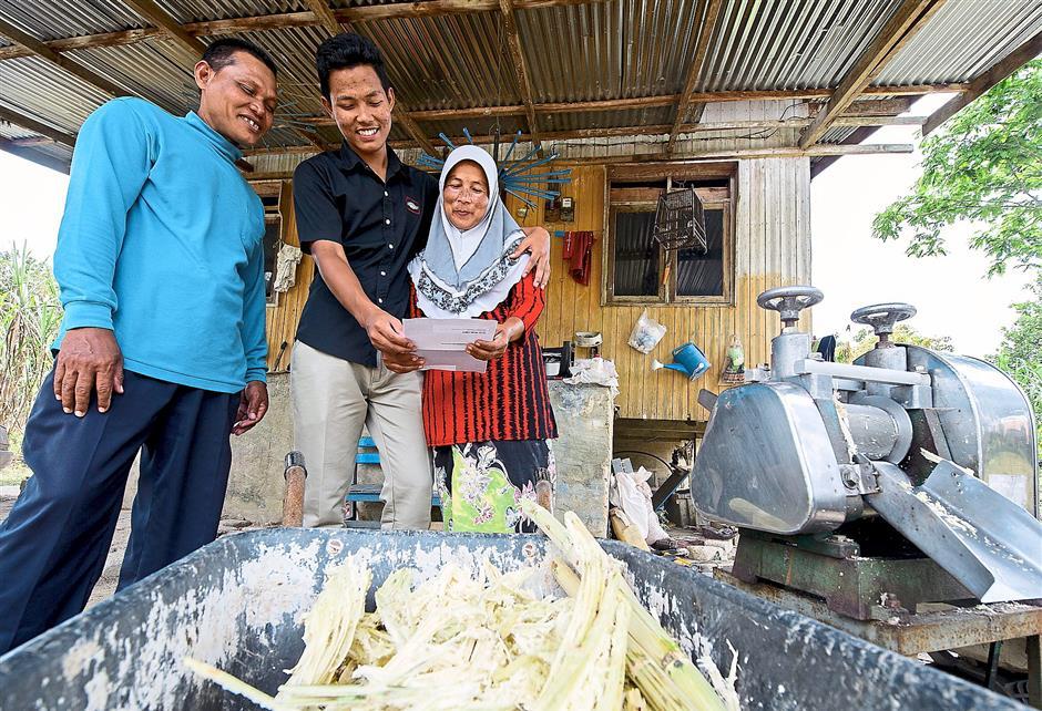 No sugarcoating needed: SMK Tengku Panglima Raja, Pasir Mas student Sahlan Mohd Nor shows his 5A achievement to proud parents Mohd Nor Mahmod and Zabidah Dauh. -- fotoBERNAMA