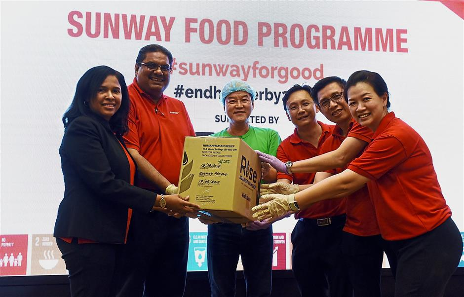 (From left) Ahila with Prakash, Rise Against Hunger Malaysia representative Bruce Tan Boon Chua, Sunway Construction general manager Lee Kuan Hong, Sunway Property Penang assistant general manager Fong Choon Fuoi and Sunway Hotel George Town sales and marketing director Michelle Koay holding a box of the meal packets.