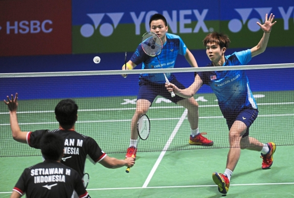 Tough challenge: Aaron Chia (left) and Soh Wooi Yik in action against Indonesiau2019s Mohammad Ahsan-Hendra Setiawan during the menu2019s doubles final of the All-England in Birmingham yesterday. u2014 AP