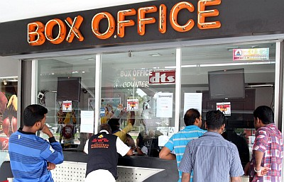 Controversial film: Cinemagoers queuing up for tickets to watch u2018Vishvaroopamu2019 in Petaling Jaya. Left: A poster promoting the movie.