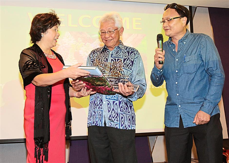 UM 1981/1982 Alumni 2014 Reunion Dinner organising committee chairman Hâ¿TMng Siew Tuan (left) giving the night's honoured guest former UM Faculty of Arts and Social Sciences dean and current Nilai University chancellor Professor Emeritus Tengku Datuk Shamsul Bahrin (middle) a token of appreciation, with alumni and organising committee member Foo Kok Teng (right).