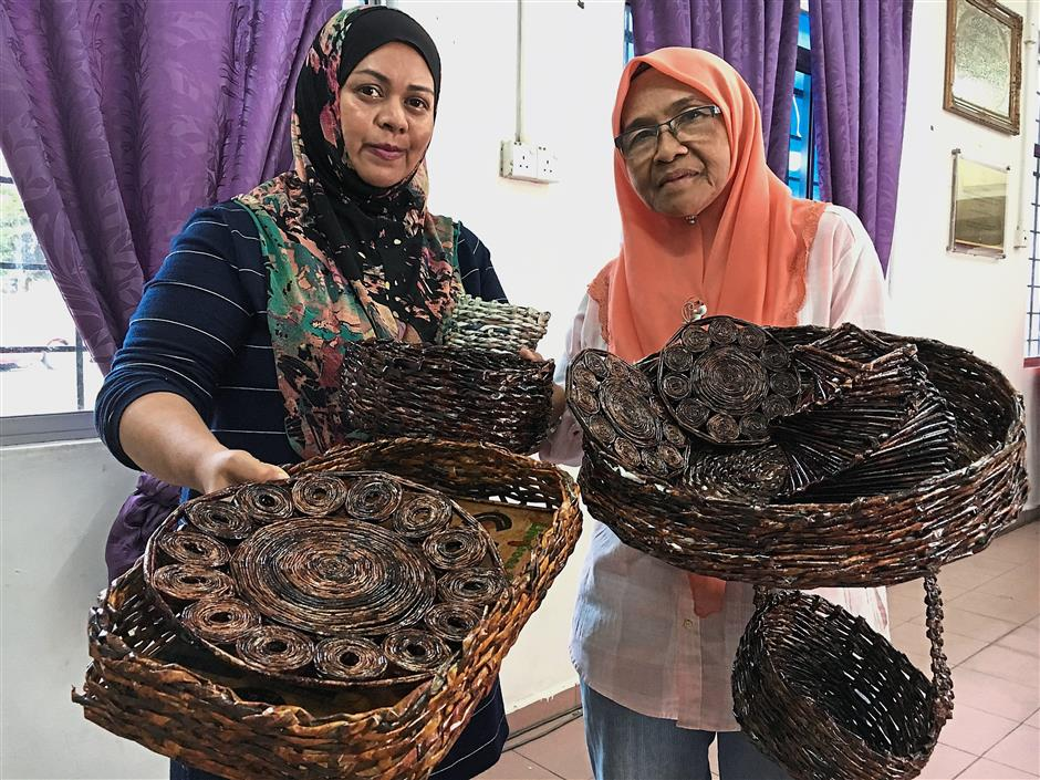 Wan Amiza (left) and Rahimah with the baskets they make using recycled paper.