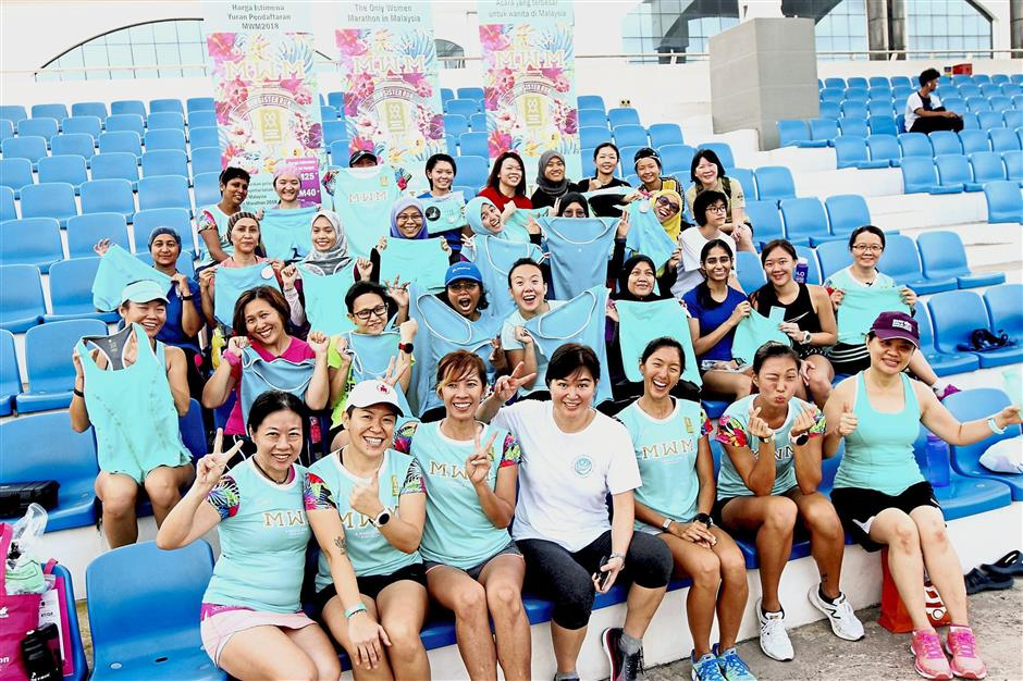 Participants showing off their teal-coloured apparel from Ash Be Nimble together with Loh (seated third from left) and Woo (in white) after the running clinic. — Photos: SAM THAM/The Star