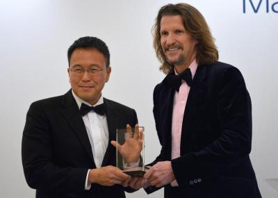 Tan (left) poses with his trophy after winning the Man Asian Literary Prize for his novel \'The Garden of Evening Mists\' in Hong Kong.