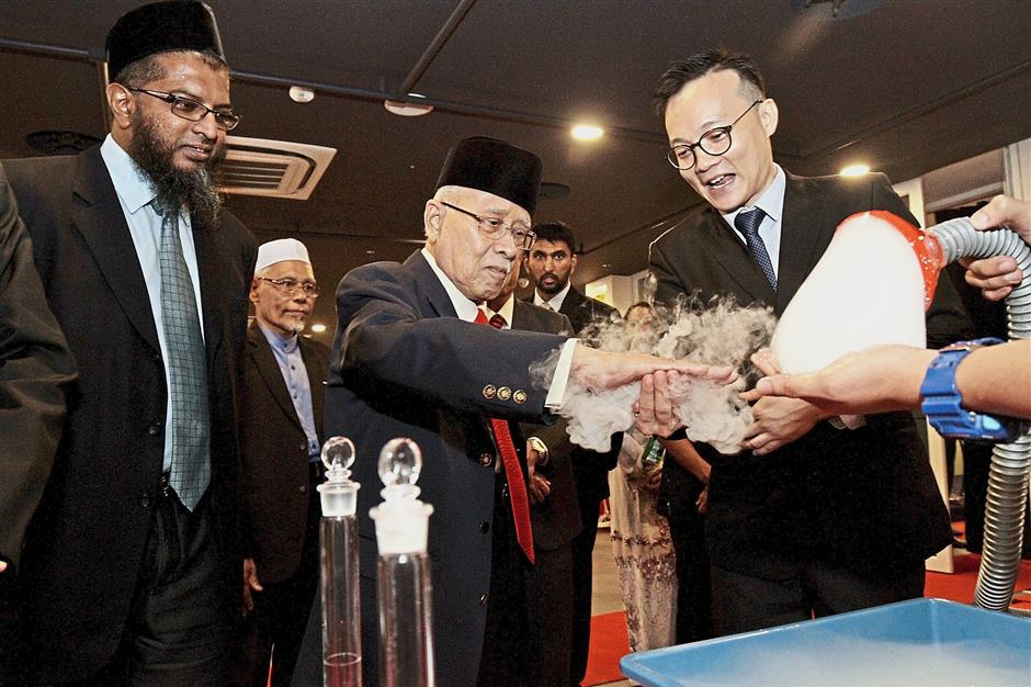 Abdul Rahman (middle) checking out an experiment, watched by National Institute of Biotechnology Malaysia research director associate professor Dr Md Azman Seeni Mohamed (left) and Tech Dome education and exhibits manager Sean Lee.