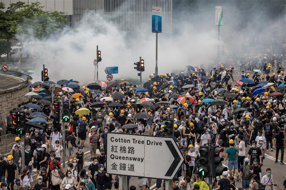 Tear gas billows over protesters during a rally against a proposed extradition law in Hong Kong, China, on Wednesday, June 12, 2019. Protesters flooding downtown Hong Kong to stop the government\'s proposed extradition law effectively presented the city\'s leaders with an ultimatum: back down, or risk violent clashes that could be worse than the Occupy movement in 2014. Photographer: Paul Yeung/Bloomberg
