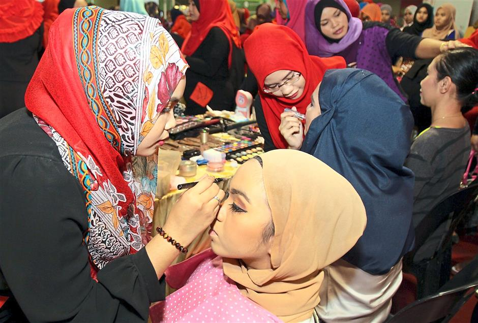 The makeup artists busy applying high-tea themed makeup on their models.