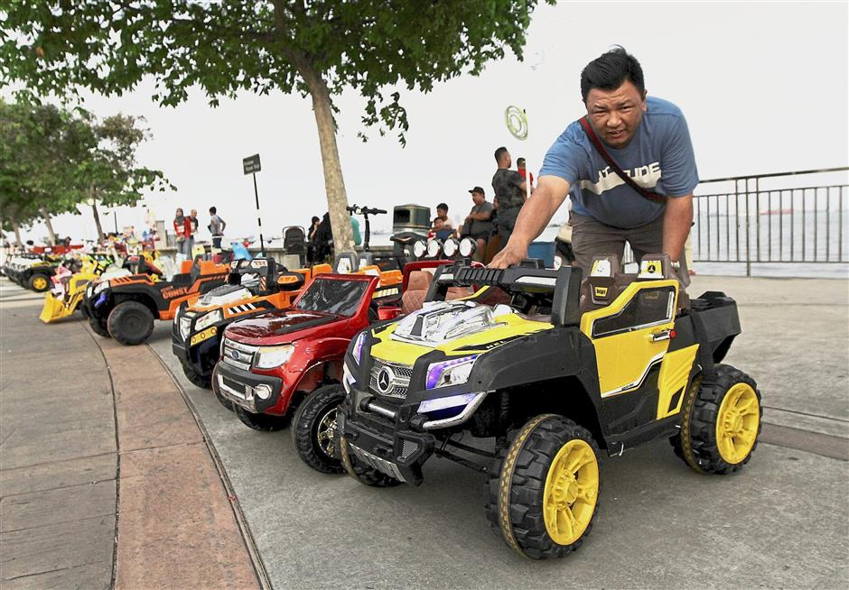 Loh arranging the toy cars that he rents out at the promenade.