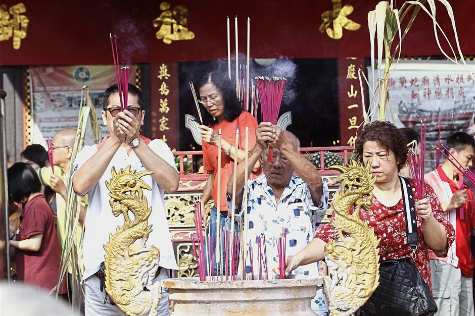 Devotees praying with joss sticks at the Snake Temple to commemorate the resident deity Cheng Chooi Chor Soo Kong's birthday.