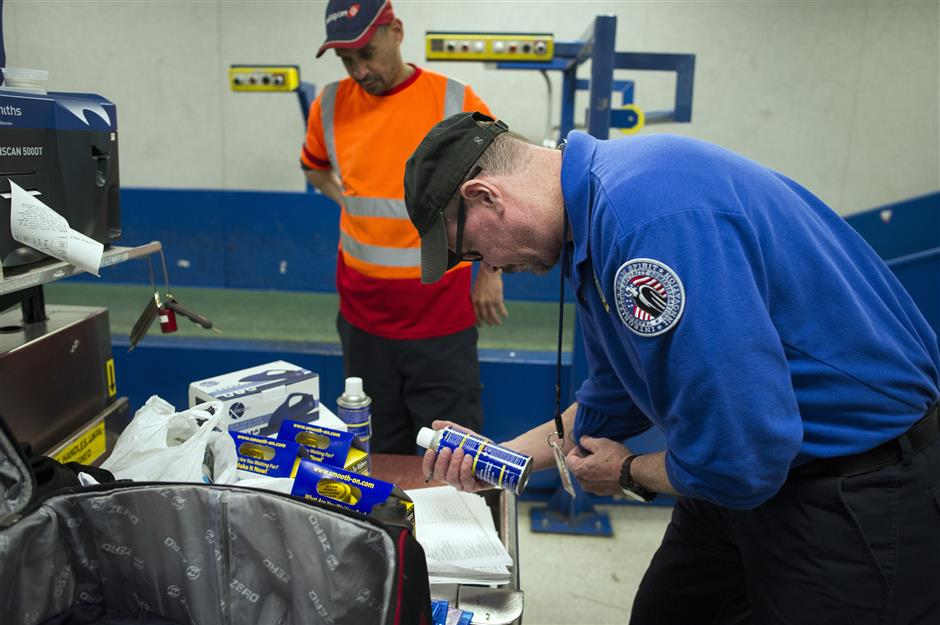 A Transportation Security Adminstration (TSA) transport security officer inspects a can which was packed in a suitcase flagged for a seconday inspection at Dulles International Airport in Dulles, Va., Tuesday, March 26, 2019. The can and the suitcase it was packed in was flagged for a secondary inspection at the intial TSA checkpoint the passenger passed through. TSAu2019s social media presence has been something of a model for other federal agencies _ striking a tone is humorous, but still gives travelers informational dos and donu2019ts. (AP Photo/Cliff Owen)