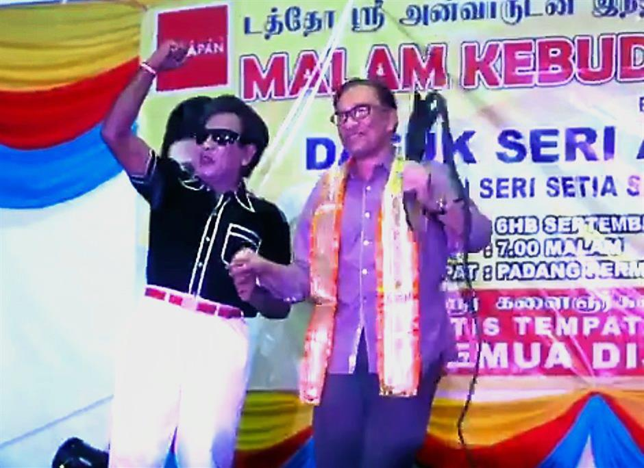 Still strong: Anwar showing off his moves as he dances on stage with the MGR impersonator at Desa Mentari in Petaling Jaya.