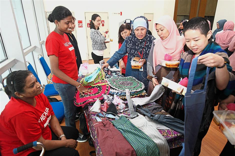 (Left and far left)Guests at the launch of the Fabric Recycling Initiative checking out the recycled items re-purposed from unwanted textile waste on display at the event.