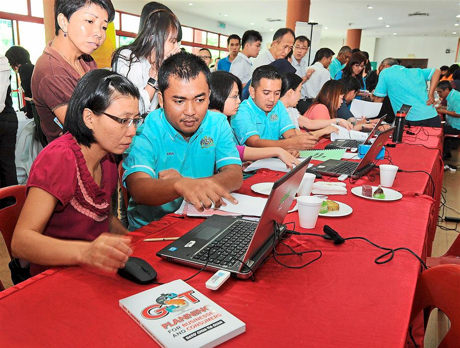 Show how it's done: A Royal Customs Department officer taking a business owner through GST registration at a GST seminar in Southern University College, Johor Baru last October. — filepic
