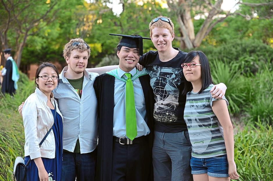 Red-letter day: Geoffrey (centre) graduated in 2012 from Monash University. His younger sister Shannen is currently a student there.
