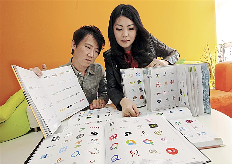 Khaw and Jasmine showing some of the company's logos that are included in the Logolounge reference books for designers.