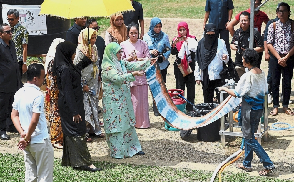 Tunku Azizah examining a finished product at the workshop.