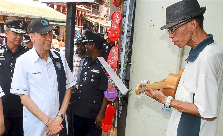2 Vice-chairman of the MCPF malaysiaTan Sri Datuk Seri Lee Lam Thye make the walk about during the crime prevention campaign tourist and trader at Jonker Walk Melaka ,Looking also Melaka police chief Datuk Chuah Ghee Lye.