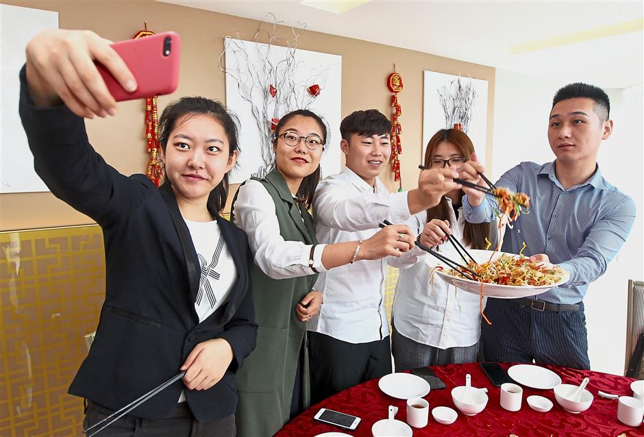 (From left) Lyu, Zhang, Chen, She Ke Xin and Su Shen take a wefie as they toss the yee sang during a mini Chinese New Year celebration at UCSI's Le Quadri Hotel.
