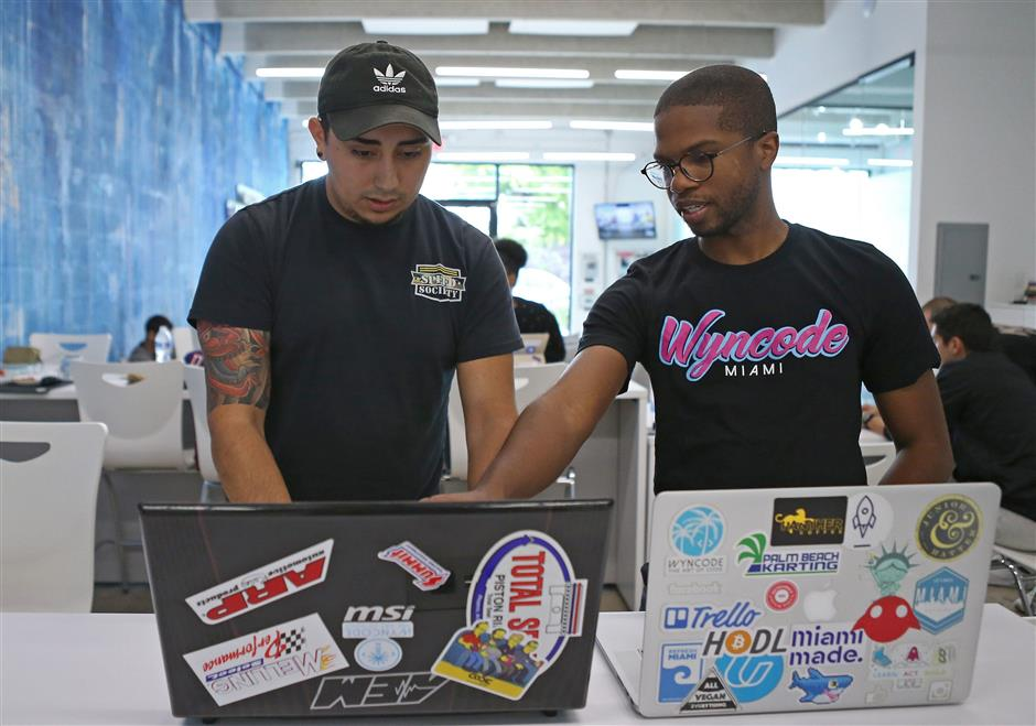 Wyntalent UX designer and Teaching Assistant Calvin Simms works with one of the students Cristian Ospina at the Wyncode Academy on Wednesday, July 18, 2018, in Miami. (David Santiago/Miami Herald/TNS)