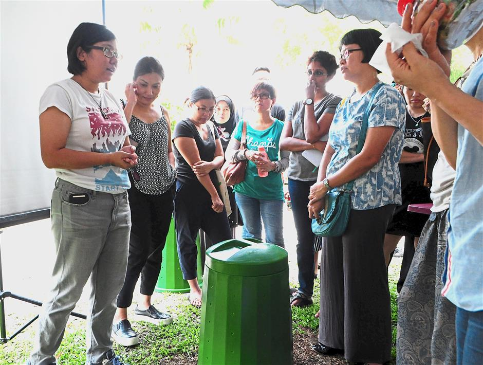 Nabila (left) conducting the workshop on backyard composting with Taman Putra Prima Fasa 2 residents.