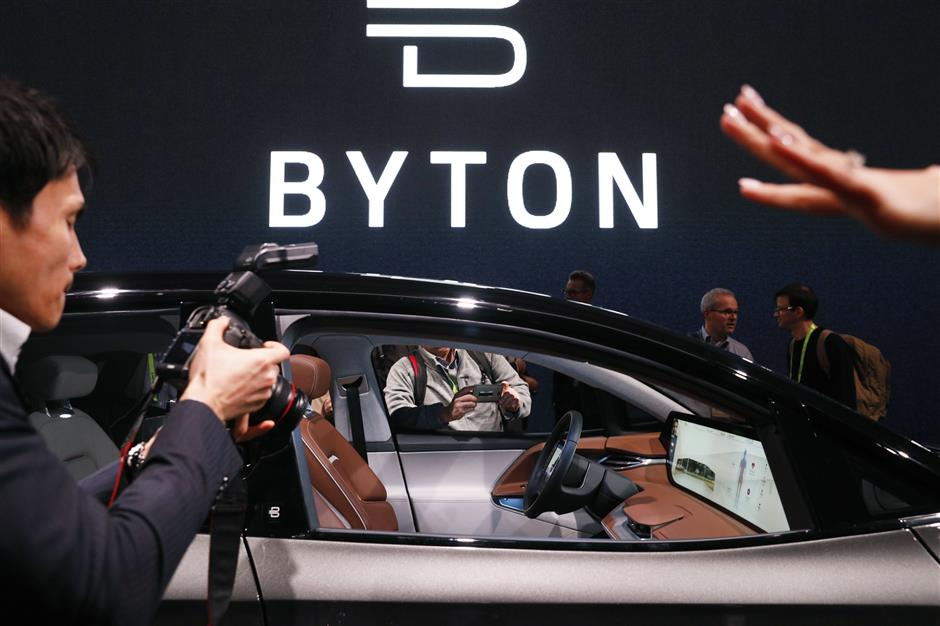 People photograph a car before a Byton news conference at CES International, Sunday, Jan. 6, 2019, in Las Vegas. (AP Photo/John Locher)