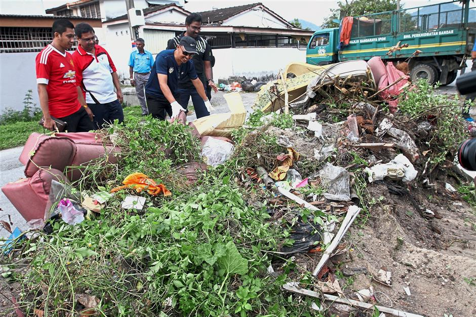 Mohd Alias (wearing cap) joined council workers in clearing rubbish from a dumpsite in Taman Merdeka during the gotong royong.