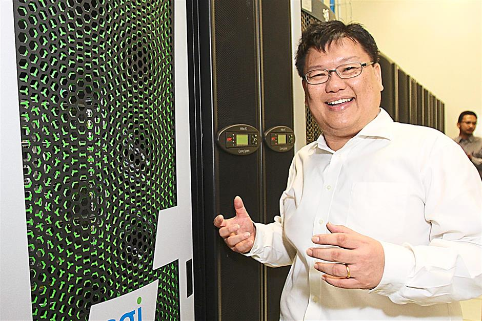 Prof Dr Wan Kiew Lian showing off a high-performance computer at the Malaysia Genome Institute which is used for number-crunching, processing the data from DNA sequencers elsewhere in the facility.