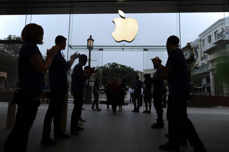 Apple employees awelcome the first shoppers arriving to purchase the new Apple iPhone 5S and 5C, at the Apple Store at the Americana at Brand shopping complex in Glendale, California, Sept 20, 2013. According to Nielsen, US consumer confidence is hitting a six-year high in Q3 this year - AFP Photo.