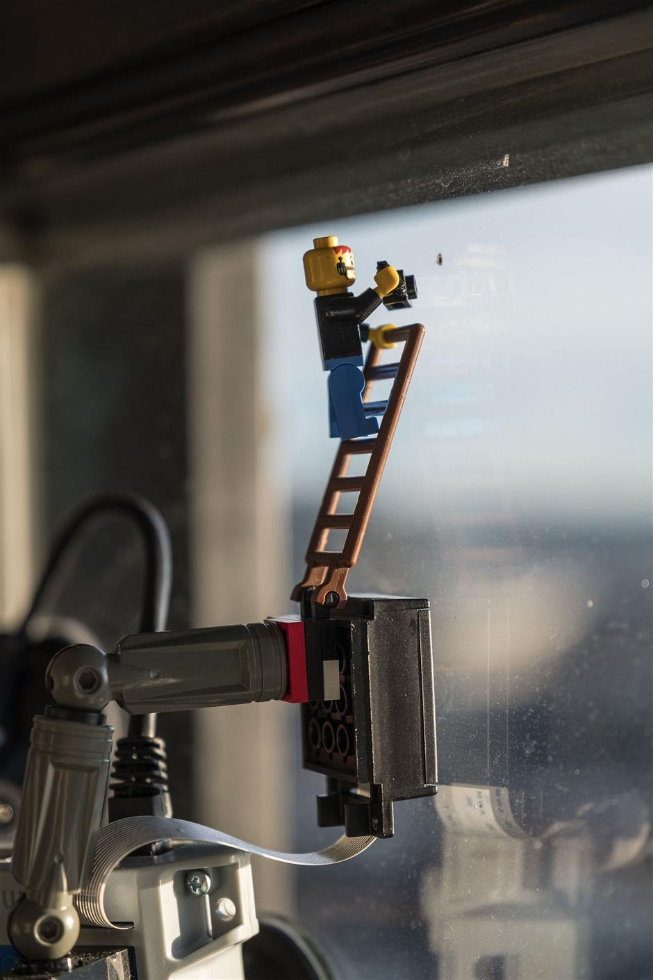 On top of Hussey's web cam is a Lego figure of a camera man on a ladder. From Alan Hussey's 19th floor window inside Smith Tower he gets an unobstructed view of sunset over Elliott Bay and the Olympic Mountains. He captures it on a web camera -- mounted here on his office window -- and posts it every day on Twitter at @GoldenHourSEA. (Dean Rutz/Seattle Times/TNS)