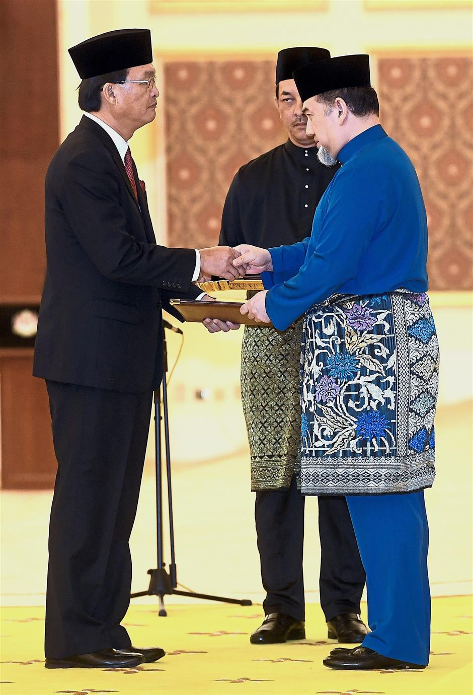 Yang di-Pertuan Agong Sultan Muhammad V (right) hands over the letter of appointment to Baru Bian at the swearing-in ceremony yesterday. u2014 Bernama