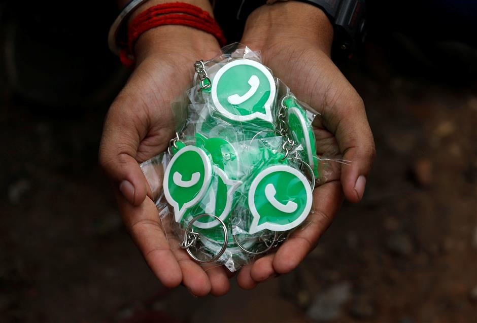 A WhatsApp-Reliance Jio representative displays key chains with the logo of WhatsApp for distribution during a drive by the two companies to educate users, on the outskirts of Kolkata, India, October 9, 2018. Picture taken October 9, 2018. REUTERS/Rupak De Chowdhuri