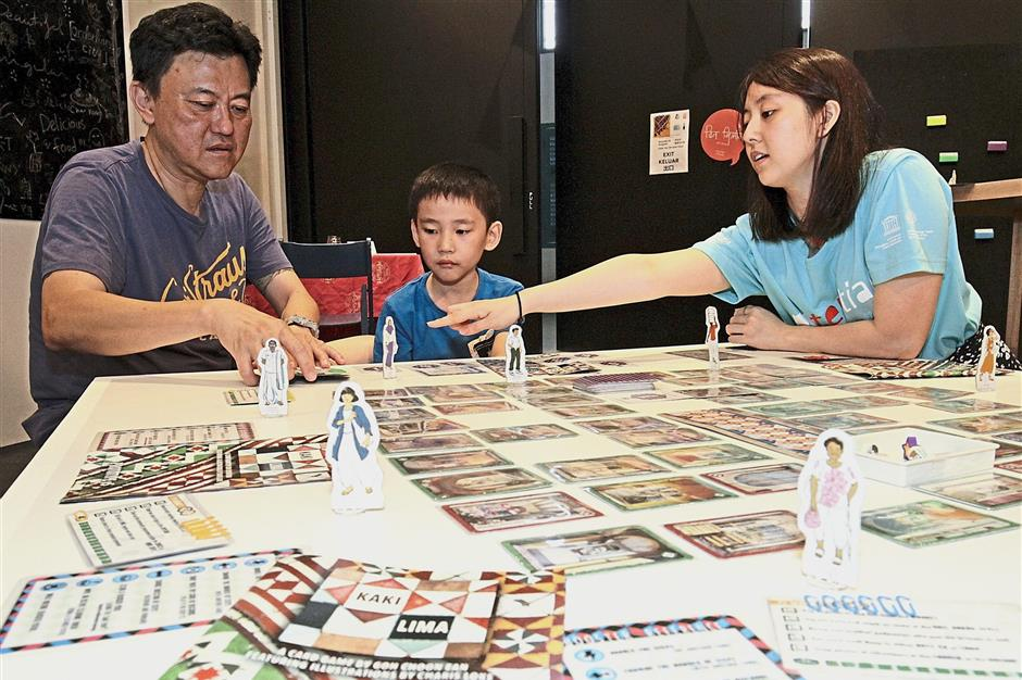 Volunteer Rebecca Yeoh (right) explaining a card game to Yap Chee Fean, 50, and his son Edmund Yap, seven, at the event in George Town.