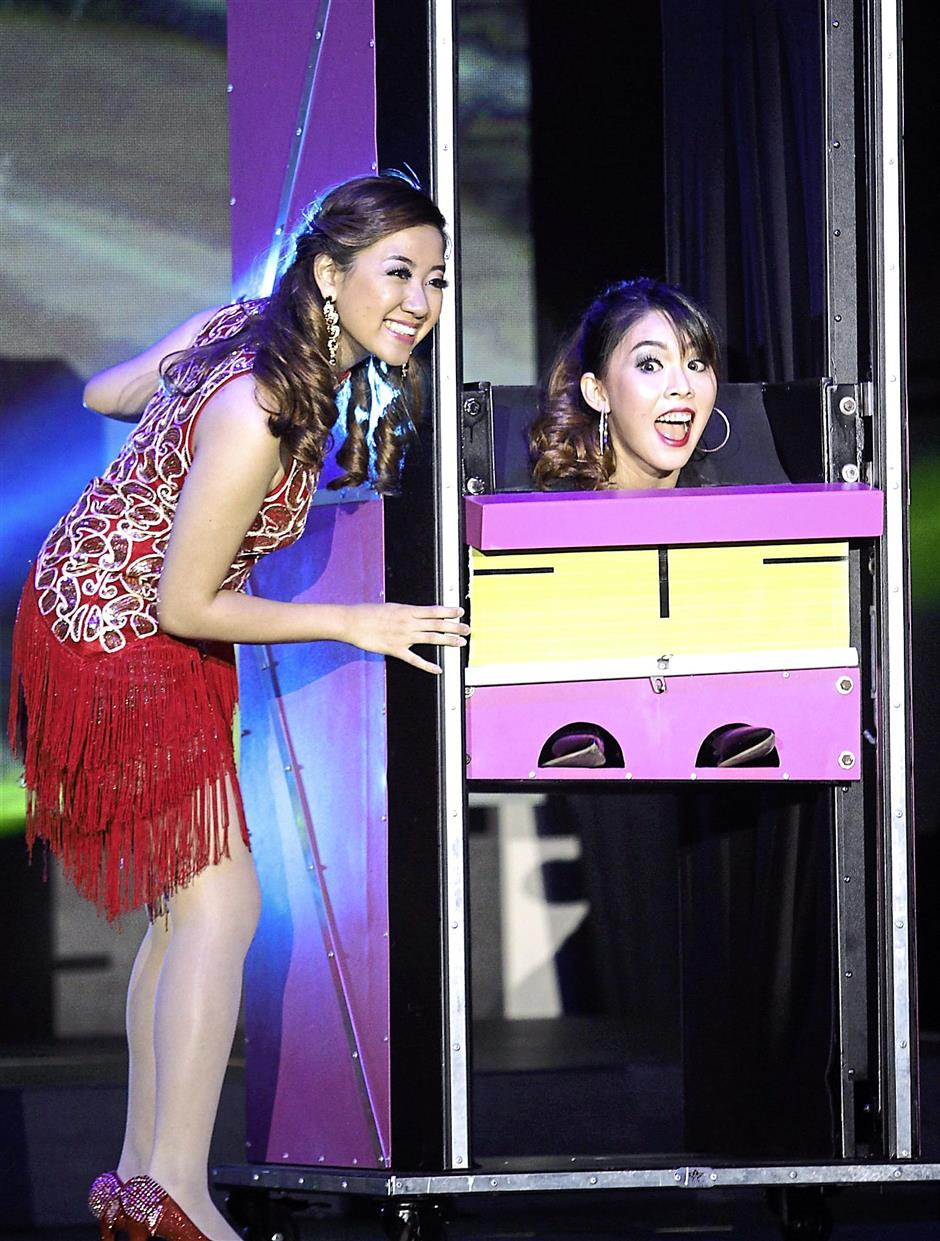 Where is she?: Miss Malaysia Tourism Metropolitan 2014 Joey Ong (right) performing a magic trick with guest performer Jorinn Chee Ka-Yee.