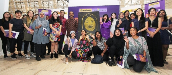Women artists at the exhibition. Pictured in the centre is an artwork of Maybank chairman Datuk Mohaiyani Shamsuddin.