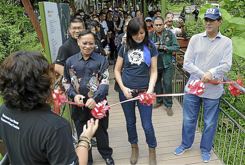 (From left) Sabah Wildlife Department director Datuk DrLaurentius Ambu, Land Empowerment Animals People (LEAP) executivedirector Cynthia Ong and Sabah Forestry Department director Datuk SamMannan cutting a ribbon at the entrance to the Bornean Sun BearConservation Centre prior to the soft opening.