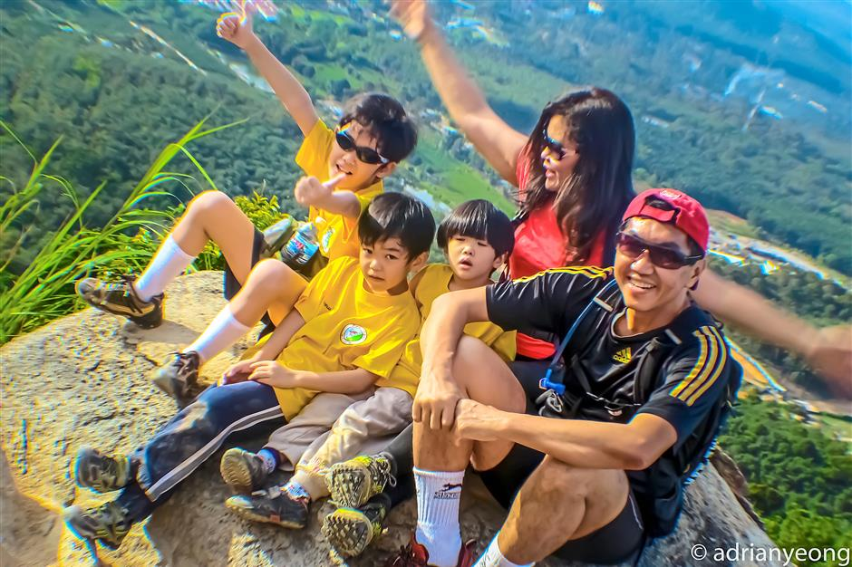 The writer with her husband, Adrian Yeong, and their kids on the peak of Broga Hill, Selangor.