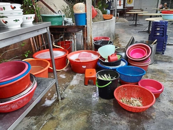 A dishwashing area filled with unwashed utensils and leftover food.