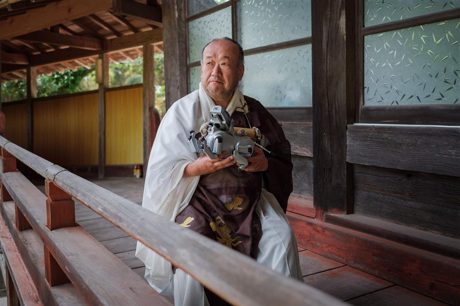 Kofukuji temple chief priest Bungen Oi holds a Sony's pet robot AIBO after a robots' funeral at the Kofukuji temple in Isumi, Chiba on April 26, 2018. More than a hundred robot dogs from different years were sitting next to each other in Japan -- it was not for a tech fair but for their 'funeral'. / AFP PHOTO / Nicolas Datiche