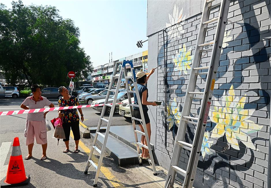 Street art: Two women on their morning shopping run stopping to admire the painting of 'Freedom', on the side-lane wall next to the Crab Factory in Jalan SS2/64, by King and Queens.