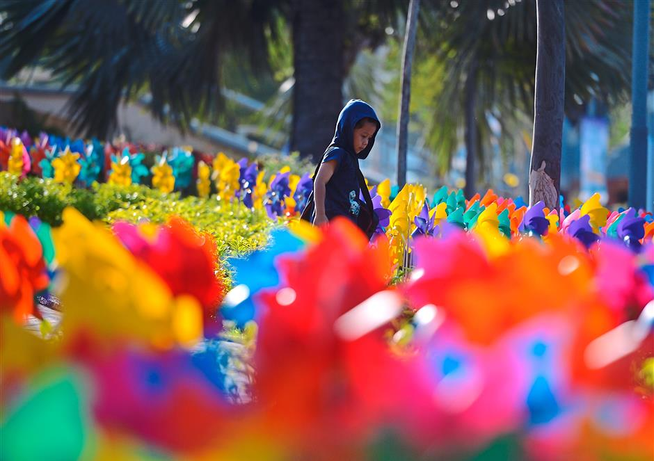 A kid playing at the colourful Pinwheel Garden.
