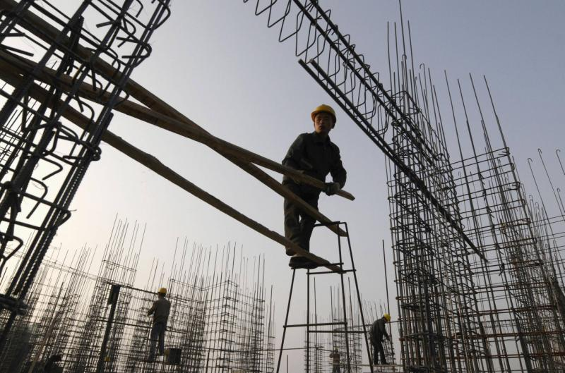 Labourers work on scaffoldings at a construction site in Changzhi, Shanxi province in this file photo. Asian markets were cheered that Beijing reported a growth of 7.3% in the fourth quarter - Reuters Photo.