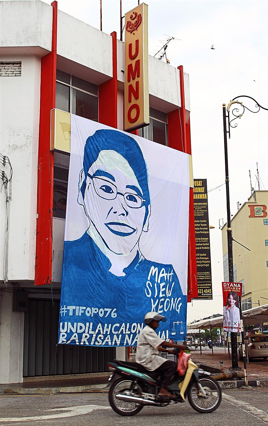 iphnoturn200514... A motorcyclist riding by a giant painting of Gerakan president and Teluk Intan parliamentary seat by-election candidate Datuk Mah Siew Keong hung on facade of the Teluk Intan Umno building at the town centre.