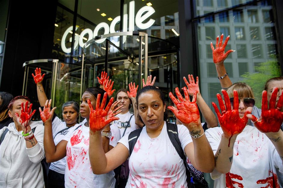 Anti-knife crime activists, with their hands painted red to represent blood, demonstrate outside the UK offices of Google in London on May 10, 2019. - Around 20 female anti-knife protesters smeared themselves with fake blood outside YouTube's London offices in protests at the Google company's allegedly lax approach to taking down violent videos. Activists from the newly-created Operation Shutdown campaign group have been targeting social media platforms such as YouTube in a bid to draw attention to the amount of graphic content online. (Photo by Tolga AKMEN / AFP)