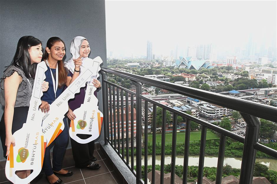 New homeowners (from left) Elaine Lim, Reshvinder Kaur and Nurhadzlin Hamden, after being presented with mock keys, checking out the view that awaits them when they move in to their Sentulmas Rumawip units. — Filepic