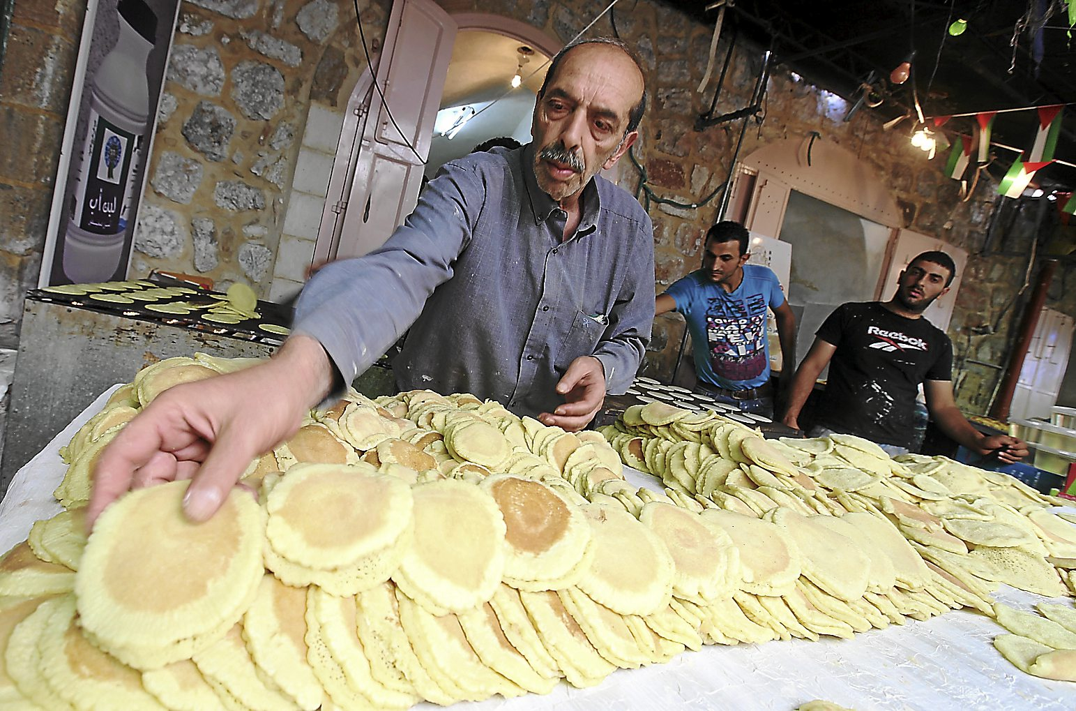 Palestinian bakers prepare traditional Ramadan pancakes called Qataiyef, or Katayef, in the Old City in the West Bank town of Hebron. The sweet is filled with cream or cheese and nuts. - EPA