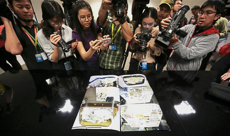 Visual proof: Journalists taking photos of images of items seized in the 1MDB probe during a press conference at the CCID headquarters in Kuala Lumpur. (Inset) Comm Amar briefing the press on the items seized. — The Star / Reuters