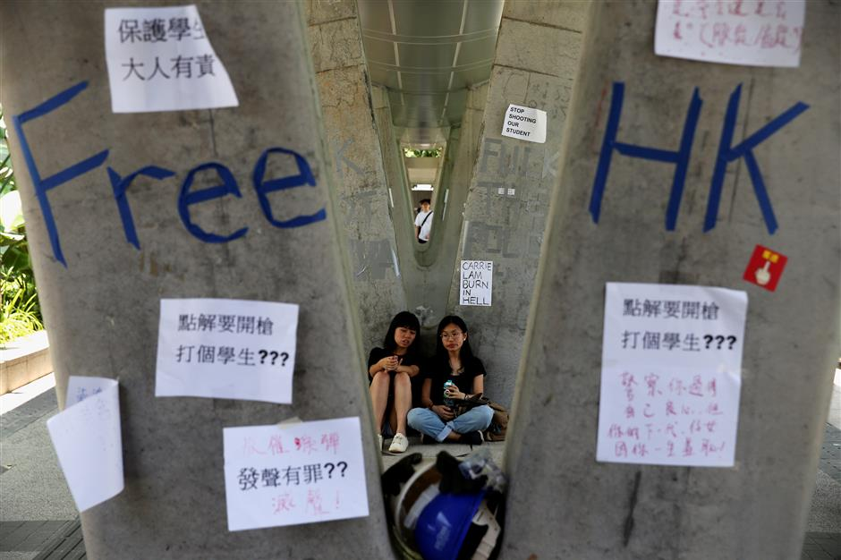 People sit next to posters and signs placed following protests against the proposed extradition bill, in Hong Kong, China June 14, 2019.  REUTERS/Athit Perawongmetha