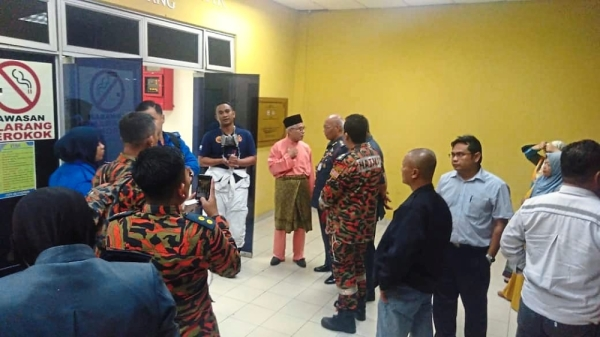 Hassan (wearing songkok) visiting the operations centre to get updates on the situation last week. — Filepic