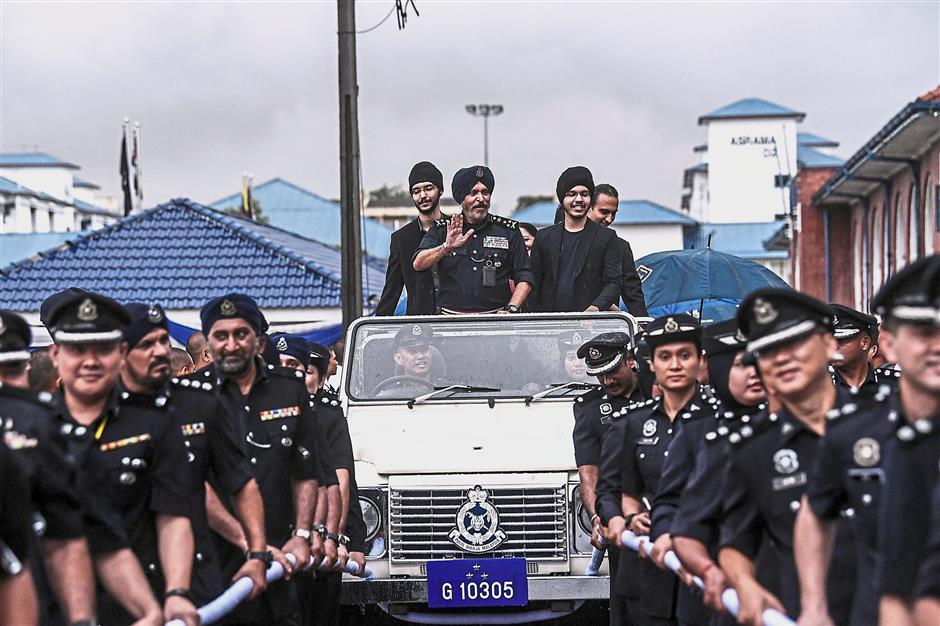 Riding high: Comm Amar, with his sons, waving from a ceremonial vehicle at the Police Training Centre. — Bernama